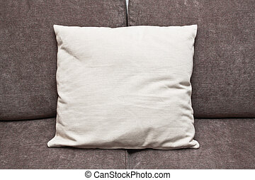 Cushion - An off-white cushion on a brown sofa