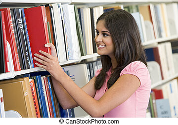 University student selecting book from library - Female...