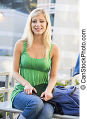 Female student sitting outside
