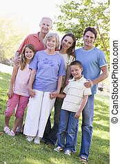 Extended family standing in park holding hands and smiling