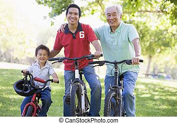 Grandfather son and grandson bike riding