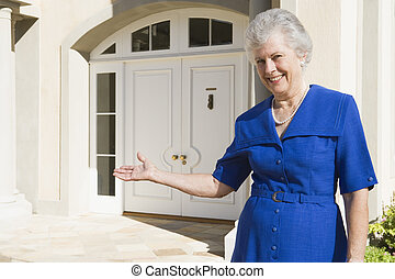 Senior woman standing outside home - Senior woman welcoming...