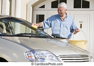 Senior man washing car - Senior man wasing car with sponge...