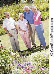 Group of senior friends in garden Group of senior friends in...