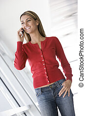 Woman standing in corridor using cellular phone smiling