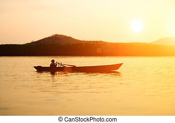 Silhouette of local small fishing boat moving in the Phang...