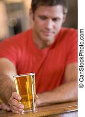 Young man relaxing at a bar with a beer
