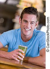 Young man enjoying a beer at a bar