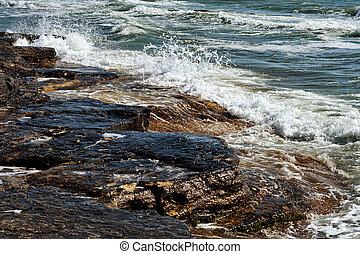 Waves break on the rocks.
