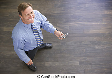 Businessman standing indoors holding cellular phone smiling