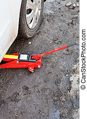 lifting car by red jack outdoors - seasonal replacement of...