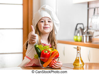 kid girl weared as cook with vegetables at kitchen