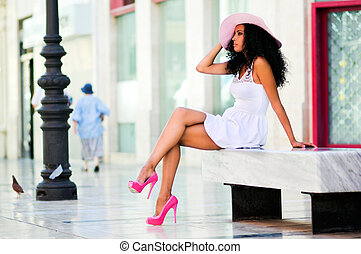 Young black woman wearing dress and sun hat, afro hairstyle...