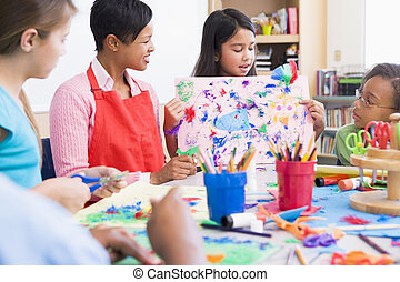 Elementary school pupil in art class showing picture to...