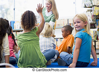Kindergarten teacher reading to children in library, girl...