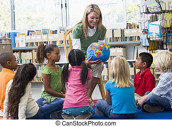 Kindergarten teacher and children looking at globe in...