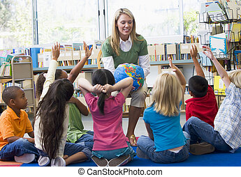 Kindergarten teacher and children with hands raised in...