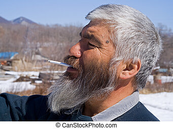 Smoking Man with Beard 2 - A portrait close-up of the old...