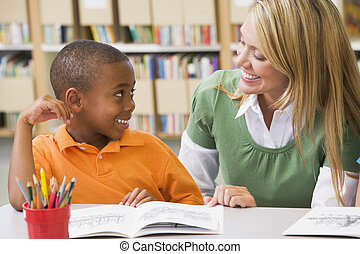 Kindergarten teacher helping student with reading skills