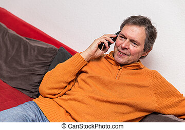senior adult on a couch with phone