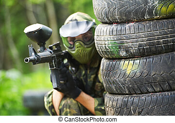 paintball player in protective uniform and mask aiming...
