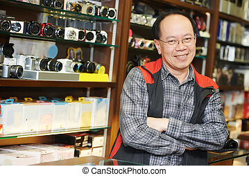 Seller at photo camera shop - Assistant seller help buyer by...