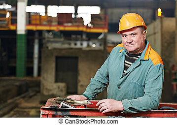 Happy industry worker at factory - portrait of positive...