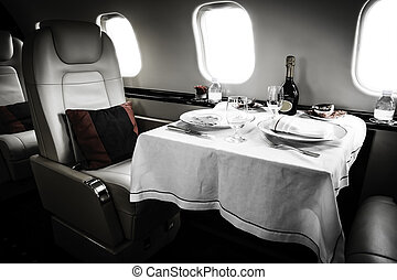 Luxury Business Jet Interior with served table and leather...