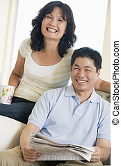 Couple relaxing with a newspaper and smiling