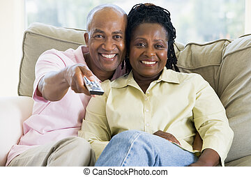 Couple relaxing in living room holding remote control and smilin