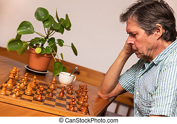 senior adult is playing chess