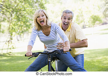 Couple on bike outdoors smiling and acting scared