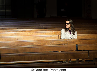 Woman praying in church and looks invisible presence to his...