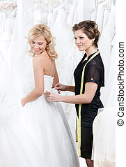 Shop assistant helps to the bride to put the dress on