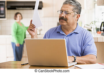 Man in kitchen with laptop and paperwork with woman in backgroun