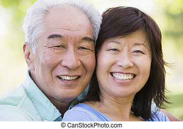 Couple relaxing outdoors in park smiling