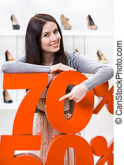 Woman showing the percentage of sales on heeled shoes in the...