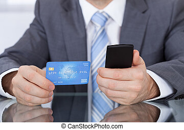 Businessperson Using Phone Card - Close-up Of Businessperson...