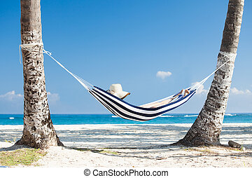 Woman In Hammock At Beach - Woman relaxing in hammock at the...