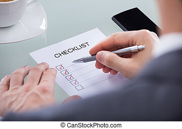 Businessperson With Pen Over Checklist - Close-up Of...