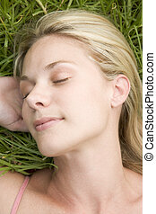 Young woman resting on grass overhead view