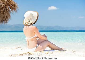 Woman in bikini enjoying the ocean view - Rear view of woman...