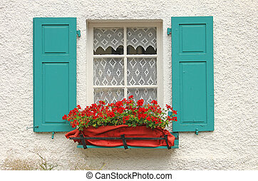 Decorative wooden window with flowers and green shutters in...