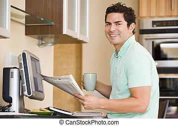 Man in kitchen with computer holding newspaper and coffee...