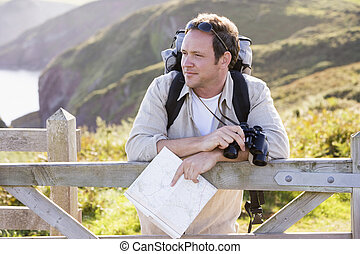Man relaxing on cliffside path holding map and binoculars