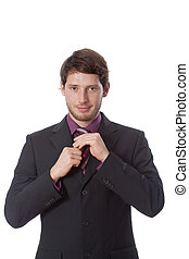 Successful man correcting tie on isolated view