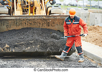Asphalt paving works - builders workers at asphalting paver...