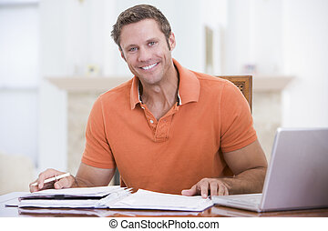 Man in dining room with laptop smiling