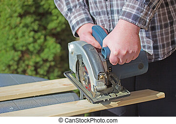 Man is working with electric circular saw - Closeup view of...