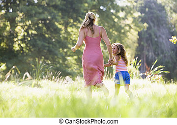Woman and young girl running outdoors holding hands and...